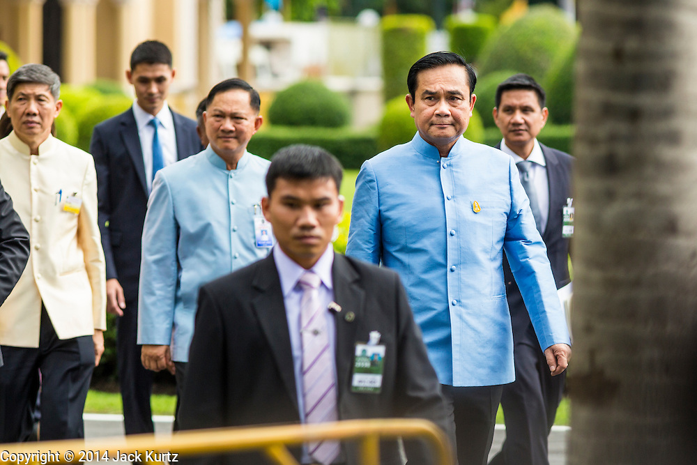 09 SEPTEMBER 2014 - BANGKOK, THAILAND: Thai Prime Minister GENERAL PRAYUTH CHAN-OCHA (center, blue shirt) surrounded by security officers, walks out to a Buddhist shrine on the grounds of Government House in Bangkok. Thai Prime Minister General Prayuth Chan-ocha named a cabinet that was dominated by members of the security forces to govern Thailand through at least a year of political reforms before elections are held. Prayuth and the cabinet met for the first time Tuesday. Before the meeting Prayuth said a prayer at a Buddhist shrine on the grounds of Government House, which is the Prime Minister's office. Prayuth seized power in a military coup in May. He was unanimously selected as Prime Minister by the National Legislative Assembly (NLA), the acting parliamentary body. Prayuth and his aides personally selected the members of the NLA after they seized power.       PHOTO BY JACK KURTZ