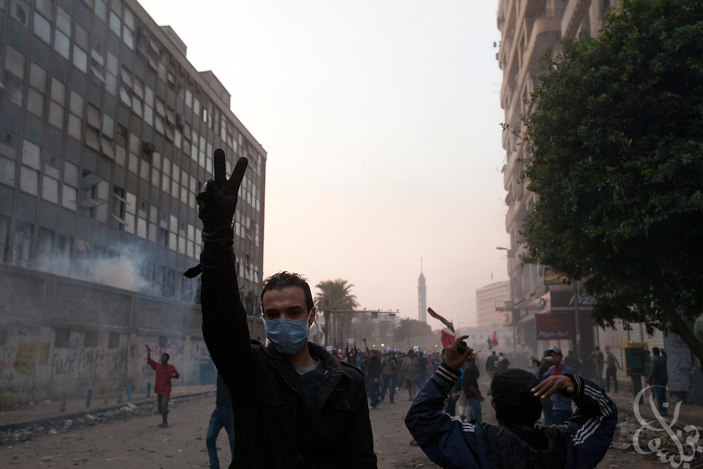 An Egyptian protestors defiantly gesture as tear gas canisters fired by nearby security forces land behind during street battles November 21, 2011 near Tahrir square  in central Cairo, Egypt. Thousands of protestors demanding the military cede power to a civilian government authority clashed with Egyptian security forces for a third straight day in Cairo, with hundreds injured and at least 24 protestors killed.  (Photo by Scott Nelson)