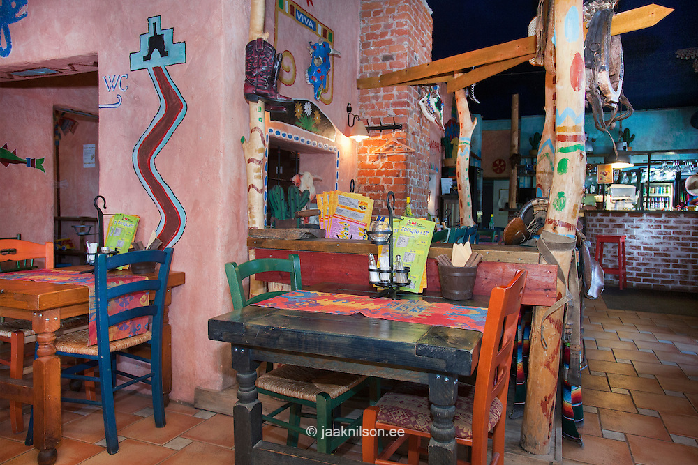 Tex Mex Mexican restaurant in Pärnu, Estonia. Decorated striped fabrics, painted symbols and blankets. Wooden furniture.