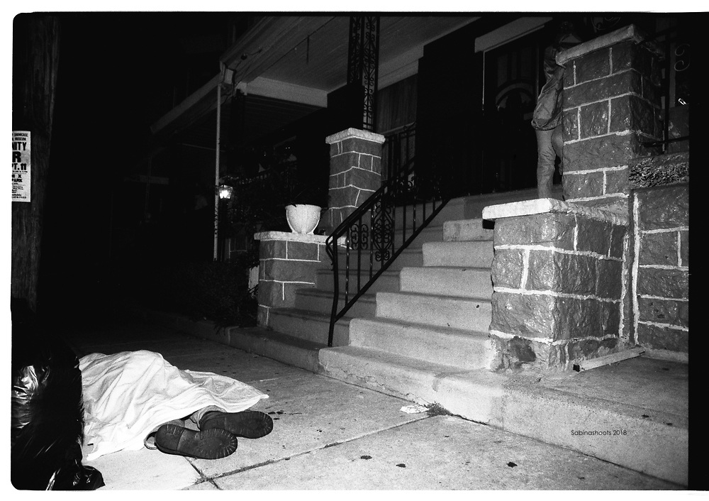 A dead man is covered by a sheet after being shot.