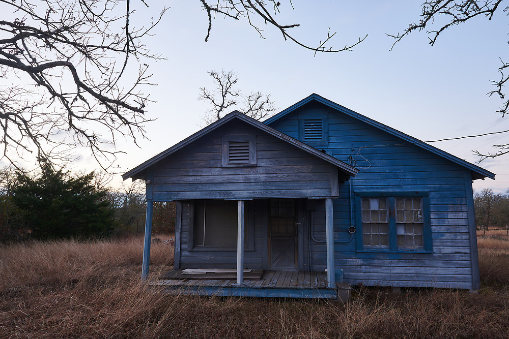 A former home is seen at dusk on a farm to market road in rural Texas.