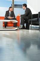 Two businessmen having meeting in lobby
