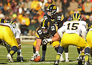 November 23 2013: Iowa Hawkeyes quarterback Jake Rudock (15) lines up behind Iowa Hawkeyes offensive linesman Austin Blythe (63) during the first quarter of the NCAA football game between the Michigan Wolverines and the Iowa Hawkeyes at Kinnick Stadium in Iowa City, Iowa on November 23, 2013. Iowa defeated Michigan 24-21.