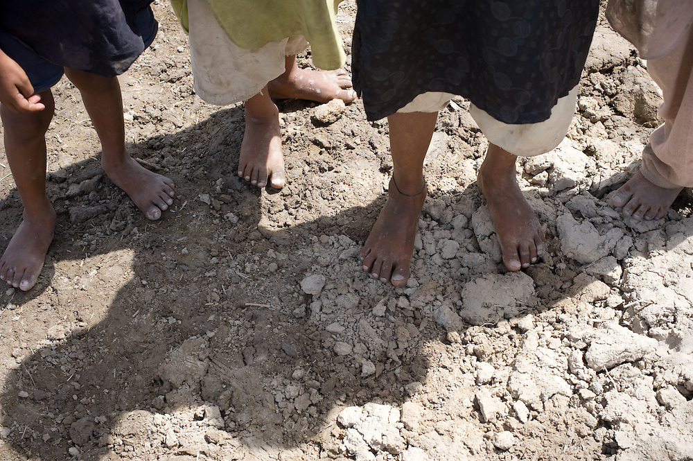 Boys' bare feet stand on the drying mudd. Floods destroyed their houses and land one month after the flooding started to cause destruction all over the country. Jamshroo, Pakistan, 2010