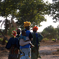 Morocco May 18, 2005 -  - Women in a country lane in Guinea with her child in her back