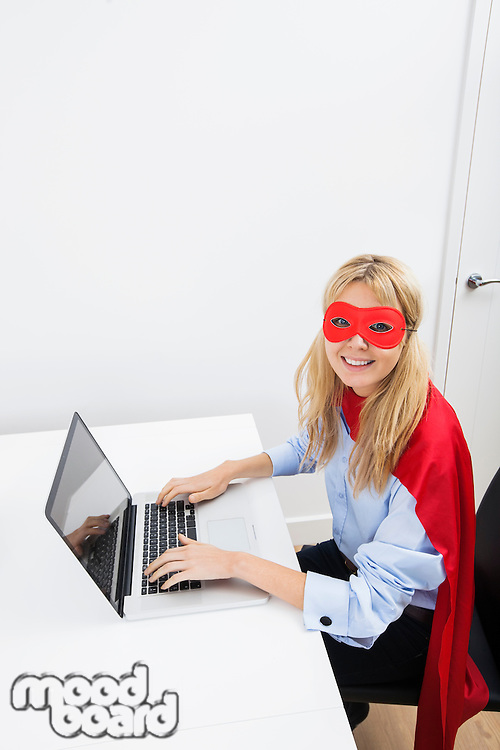 Portrait of happy businesswoman in superhero costume working on laptop in office