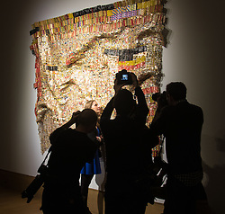 Bonhams, Mayfair, London. Photographers swarm around a woman as she admires Peju's Robe, estimated at £450,000 - 550,000, by Ghanaian sculptor El Anatsui is made from thousands of pressed bottle tops, to be auctioned at Bonhams post-war and Contemporary art sale.  ///FOR LICENCING CONTACT: paul@pauldaveycreative.co.uk TEL:+44 (0) 7966 016 296 or +44 (0) 20 8969 6875. ©2015 Paul R Davey. All rights reserved.
