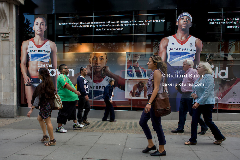 Passers-by walk beneath the inspiring images of Team GB gold medallist heptathlete Jessica Ennis and long jumper Phillips Idowu adorn the exterior of the Adidas store in central London's Oxford Street, during the London 2012 Olympic Games. The ad is for sports footwear brand Adidas and their 'Take The Stage' campaign which is viewable across Britain and to Britons who have been cheering these athletes who have been winning medals in numbers not seen for 100 years. Their heroic performances have surprised a host nation who until the victories, were largely anti-Olympics - now adoring their darling Ennis and her good looks.