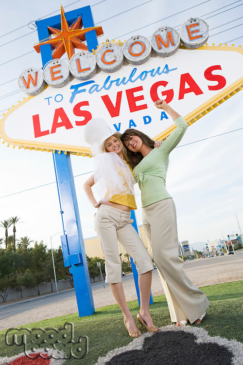 Two young female friends in front of Welcome to Las Vegas sign