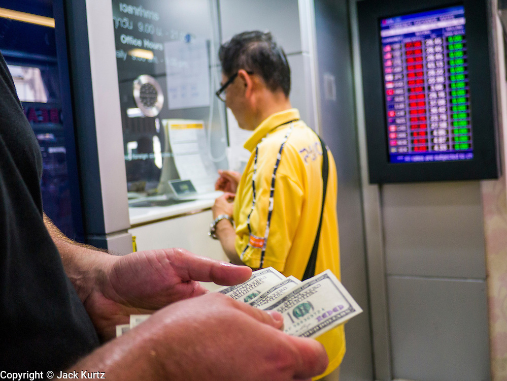 22 APRIL 2013 - BANGKOK, THAILAND:   A European tourist in Bangkok counts out his US Dollars before buying Thai Baht at a foreign exchange kiosk in Bangkok. The Thai Baht has gained markedly against the US Dollar, the Euro and Pound Sterling in recent months. On Monday, the Baht was trading at 28.57 Baht to 1 US Dollar on Apr. 22. The strengthening Baht means imported goods are cheaper in Thailand, but Thai exports cost more in other countries. It also means tourists and expats who live in Thailand have less money to spend as their currencies buy fewer Baht. The baht has risen 5 percent against the dollar this year to its highest level since before the Asian financial crisis in 1997. The Federation of Thai Industries, which has led calls for the authorities to act to lower the baht, said the rise in the past two weeks had been too rapid and its members were finding it hard to cope with the volatility because as the Baht appreciates their exports become more expensive. Thailand is among the world's leading exporters of rice, chicken, pork, electrical components, cars and is the leading exporter of canned tuna.  PHOTO BY JACK KURTZ