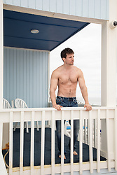 shirtless man standing on an oceanfront balcony