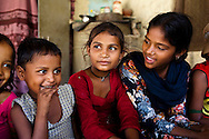 Kusum Devi (center, in red), 10, sits amongst other snake charmer's children in Naraina gaon, Titana village, Samalkha town, Haryana, India on 15th June 2012. Kusum walks to and from her school daily, one kilometer away from her village. When she is not schooling, she takes care of her family and their livestock. India's snake charmer communities suffer from a loss of livelihood because of stringent wildlife laws and are forced to resort to begging or working as daily wage labourers. A new program to encourage the snake charmer's children to attend school is underway, to keep them from becoming daily-wage child labourers or joining their parents in scavenging and begging in cities. Photo by Suzanne Lee for The National
