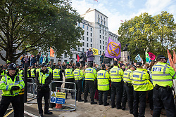 London, UK. 13 October, 2019. Metropolitan Police officers form a cordon in front of Extinction Rebellion activists protesting in solidarity with disabled climate activists outside New Scotland Yard.
