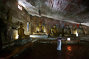 A pilgrim dressed in white carries her baby up to the sacred cave, believing it to provide protective powers, Cave Temple of Dambulla.
