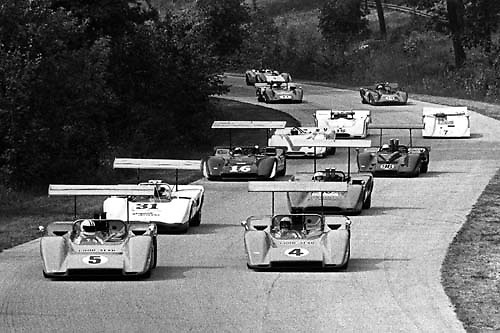 Denny Hulme (5) and Bruce McLaren (4) pace the start of the 1969 Road America Can-Am at Elkhart Lake in their pair of McLaren M8Bs, the winged wonders that won every round of that year's record 11-race season.