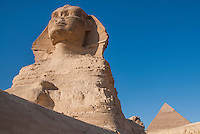 The Sphinx and a pyramid against a brilliant blue sky, in Giza, Egypt.