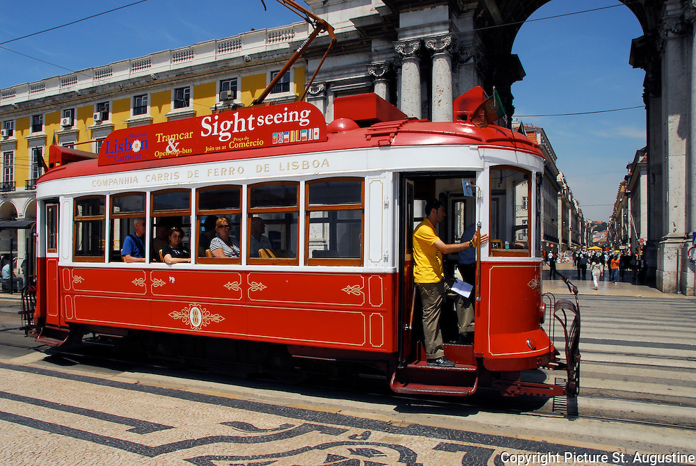 A tourist tram in front of the Rua Augusta Arch in the Praca do Comercio, Lisbon, Portugal.