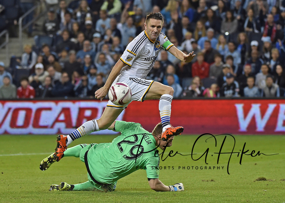 Oct 25, 2015; Kansas City, KS, USA; LA Galaxy forward Robbie Keane (7) dribbles past Sporting KC goal keeper (29) and scores during the first half at Sporting Park. Mandatory Credit: Peter G. Aiken-USA TODAY Sports