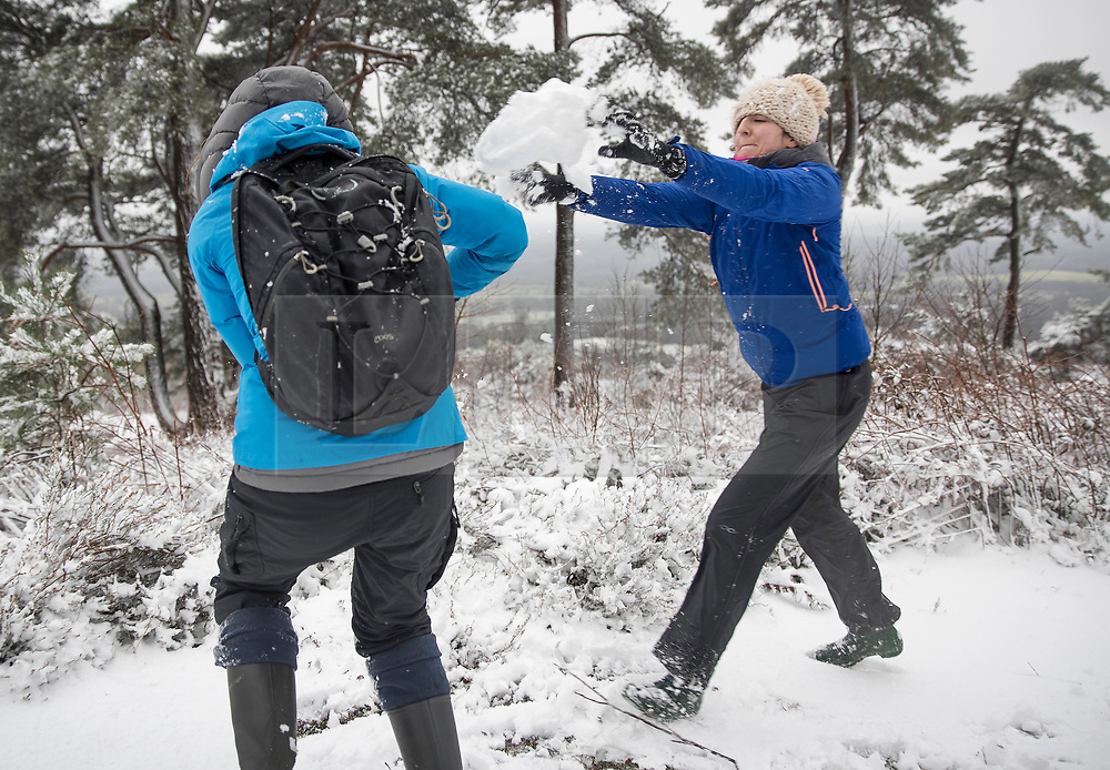 © Licensed to London News Pictures. 27/12/2017. Dorking, UK. Hill walkers Lydia Farzin-Nia (R) and Charlotte Turner have a snowball fight at the top of Leith Hill after early morning snow showers and low temperatures. Photo credit: Peter Macdiarmid/LNP