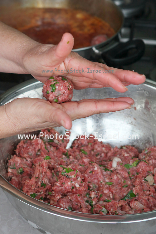 Cooking Moroccan meatballs in tomato sauce forming a meatball