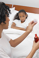 Nurse pouring medication for girl (7-9) lying in bed