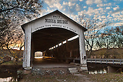 "Mecca Covered Bridge (150 feet long) was built in Burr Arch style over Big Raccoon Creek in 1873 by J.J. Daniels in historic Parke County, Indiana, USA. Golden sunset light beckons at the far opening. Puffy white clouds decorate the blue sky. The traditional ""Cross this bridge at a walk"" sign required slow vehicle speed, but traffic is now diverted to an adjacent modern bridge."