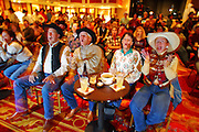"09 DECEMBER 2002 - LAS VEGAS, NEVADA, USA: Chuck McNeil, left, Gordon Aaskow, Lyndsay Matthews, and Beckie Nickerson, friends from Calgary, Canada who winter in Surprise, AZ, watch a live television feed in a bar at the Gold Coast , Dec. 9, 2002, during the National Finals Rodeo. The NFR is the ""Super Bowl"" rodeo; hundreds of thousands of rodeo fans come to Las Vegas for 10 days every December to participate, in one way or another, in the NFR. The Gold Coast hosts a number of NFR related events, including trophy presentations and free dances, during the NFR and many spectators and contestants come to the Gold Coast to watch television feeds of the rodeo and gamble. PHOTO BY JACK KURTZ"