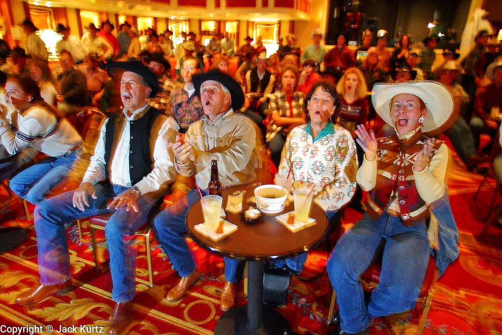 """09 DECEMBER 2002 - LAS VEGAS, NEVADA, USA: Chuck McNeil, left, Gordon Aaskow, Lyndsay Matthews, and Beckie Nickerson, friends from Calgary, Canada who winter in Surprise, AZ, watch a live television feed in a bar at the Gold Coast , Dec. 9, 2002, during the National Finals Rodeo. The NFR is the """"Super Bowl"""" rodeo; hundreds of thousands of rodeo fans come to Las Vegas for 10 days every December to participate, in one way or another, in the NFR. The Gold Coast hosts a number of NFR related events, including trophy presentations and free dances, during the NFR and many spectators and contestants come to the Gold Coast to watch television feeds of the rodeo and gamble. PHOTO BY JACK KURTZ"""