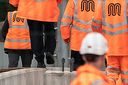© Licensed to London News Pictures. 27/07/2019. Manchester, UK. British Prime Minister BORIS JOHNSON walks along the top edge of a concrete barrier wall with an untied shoelace during a visit to an under construction area of the Trafford Line extension by Manchester's Pomona Metrolink tram stop during a visit to the city . Johnson will re-announce the HS3 rail link between Manchester and Leeds at a speech in Manchester City Centre today . Photo credit: Joel Goodman/LNP
