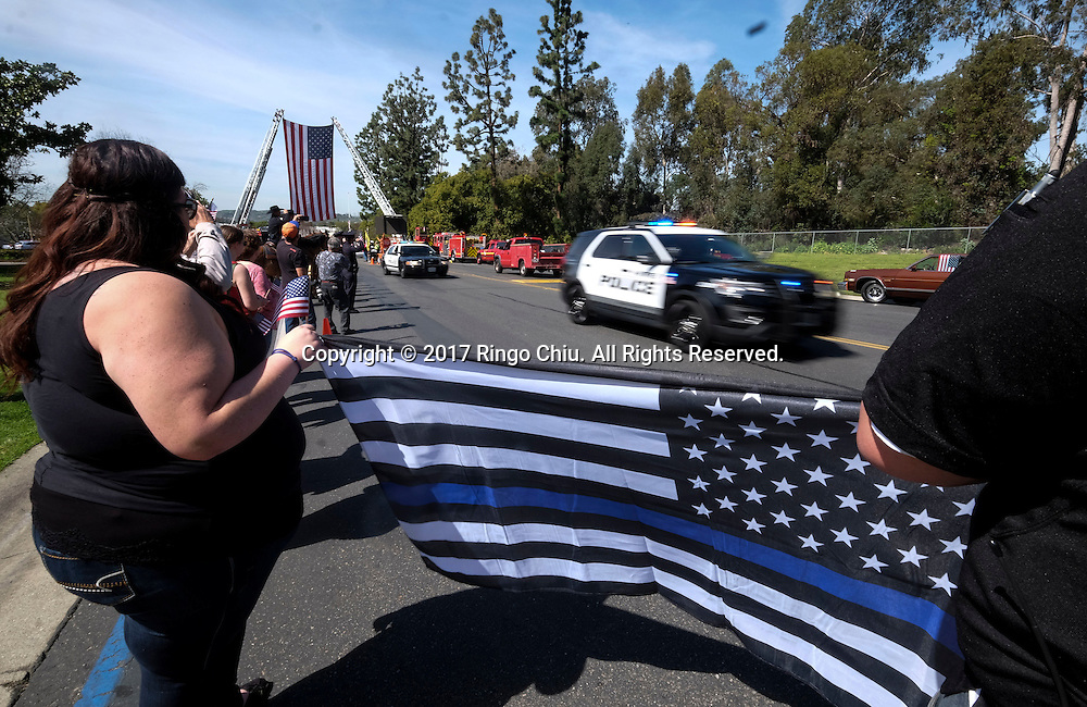 People salute as a police motorcade to honor Whittier Police Officer Keith Boyer arrives arrives at Rose Hills Memorial Park in Whittier, Calif., Friday, March 3, 2017. Boyer, who was fatally shot after responding to a traffic crash, was remembered today by thousands of law enforcement officers, friends and family as a dedicated public servant, talented drummer, loving friend and even a ``goofy'' dad.(Photo by Ringo Chiu/PHOTOFORMULA.com)<br />