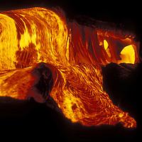 USA, Hawaii, Volcanoes National Park,  Stream of molten lava glows at night during eruption of Kilauea volcano