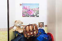 CASERTA, ITALY - 25 FEBRUARY 2015: A teady bear and the suitcases belonging to a departing Nigerian immigrant woman and ex-sex worker are here in her room at Casa Rut, a shelter for abused young immigrant women, with a stuffed given  in Caserta, Italy, on February 25th 2015. The Ursuline Sisters of Casa Rut give the young abused women a teady bear upong their arrival at the shelter.<br /> <br /> Casa Rut was founded in 1995 and it is promoted and managed by the Ursuline Sisters of the Sacred Heart of Mary of Breganze (Vicenza, Italy).  Casa Rut's goal is to provide young immigrant women a familiar environment where  they are helped to protect and free themselves, and to undertake a common path aiming to the integration in Italy's society.