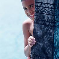 Cook Islands, K?ki '?irani, South Pacific Ocean, Aitutaki, One Foot Island, portrait of boy on boat stern