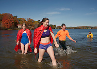 """Jill Dennis and Emily Lamot of the """"Super Heros Team"""" come out of the water at Lake Opechee during the 11th annual Turkey Plunge for the Salvation Army on Saturday afternoon.  (Karen Bobotas/for the Laconia Daily Sun)"""