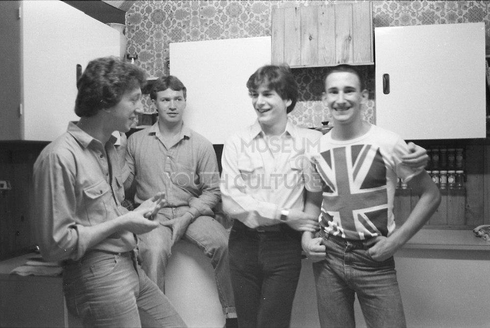 Gavin in Union Jack shirt with friends in kitchen, UK, 1980.