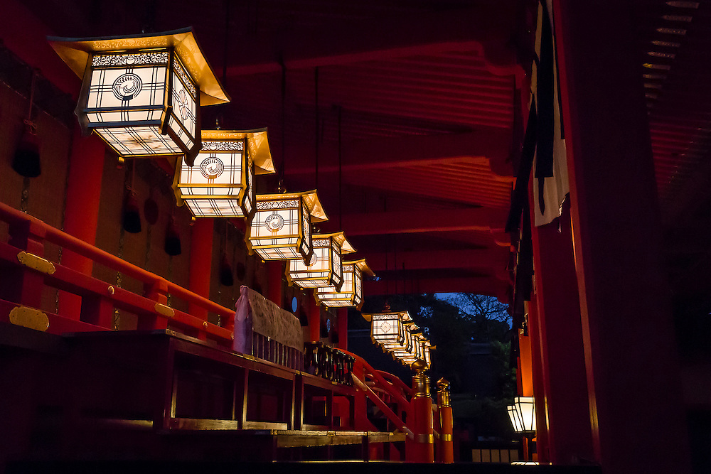 A row of lanterns is lit at Fushimi Inari's main hall when night falls.