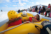 A young boy gets ready to take a ride on a rubber raft pulled over the snow by a snow mobile at the annual Sapporo Snow Festival