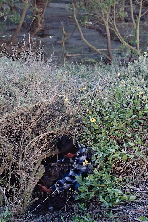 Vivere vicino alla frontiera significa dovere essere invisibili, gli elicotteri della polizia messicana sorvolano costantemente la zona, per non essere visti bisogna vivere in capanne che dall'alto sembrino cespugli. Qui Juan vive con i suoi cani.