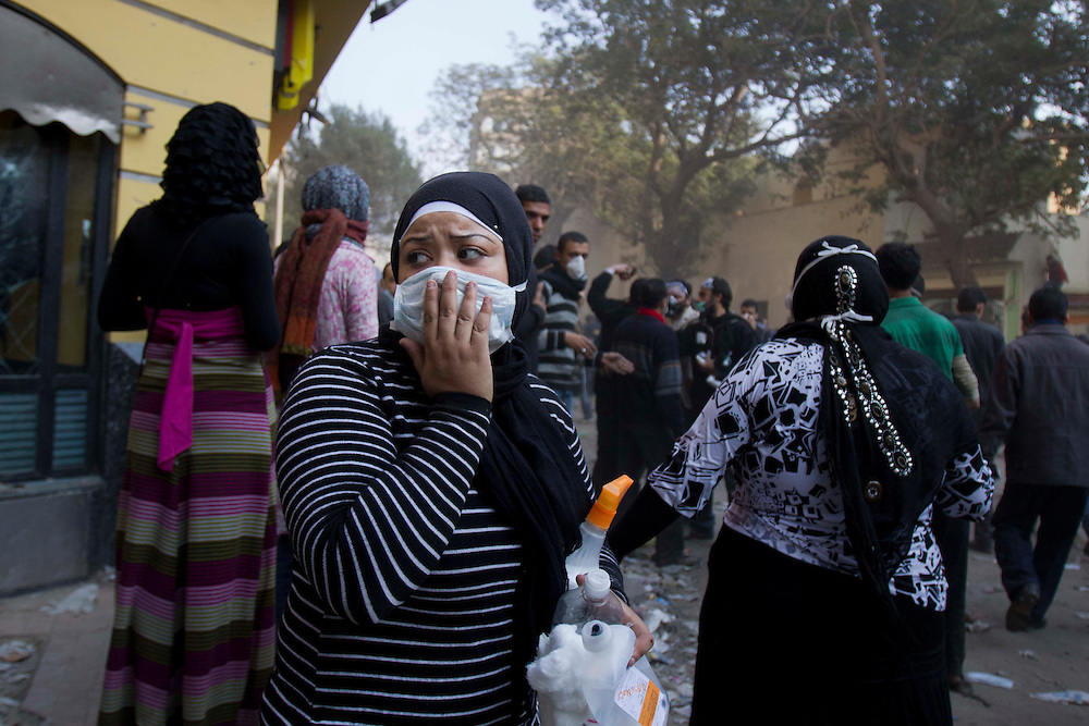 A women covers her face next to where clashes are happening between demostraters and police next to Tahrir Square on November 22, 2011 photo by: Maya Levin