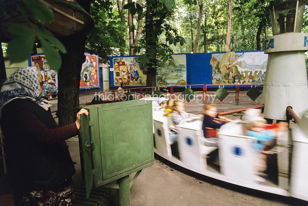 A babushka runs an amusement park ride for children, Krasnoyarsk, Russia (circa 1989)