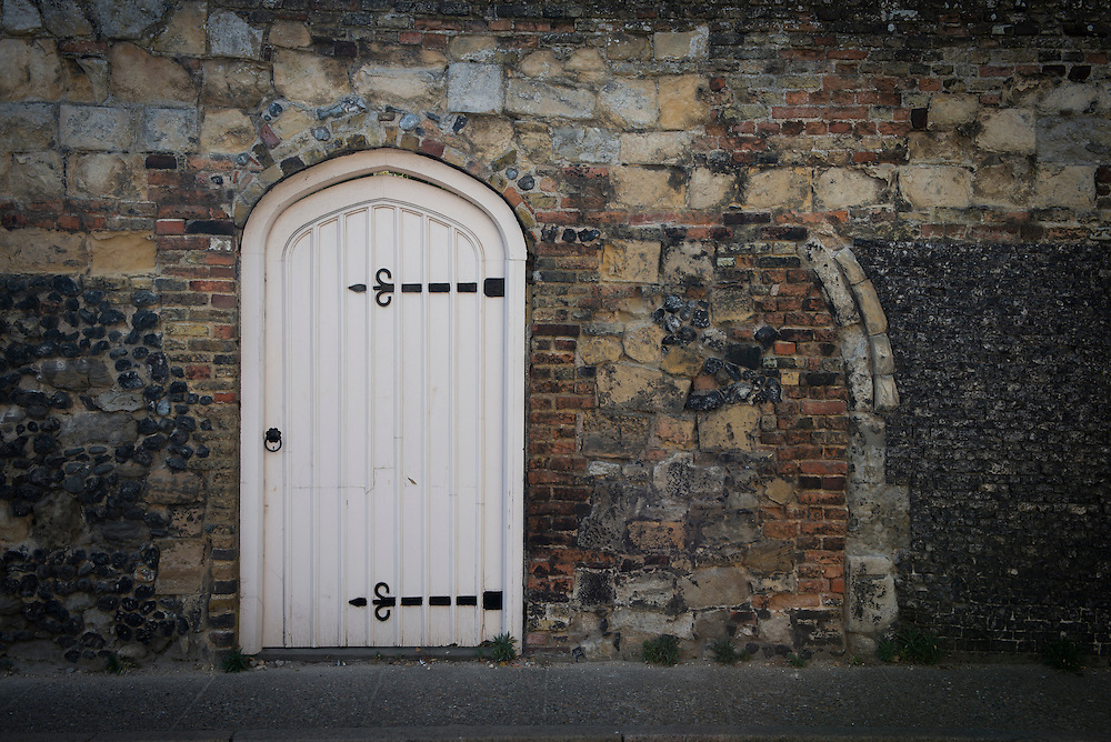 An old doorway in an ancient historical brick and stone masonry wall in Sandwich, Kent.