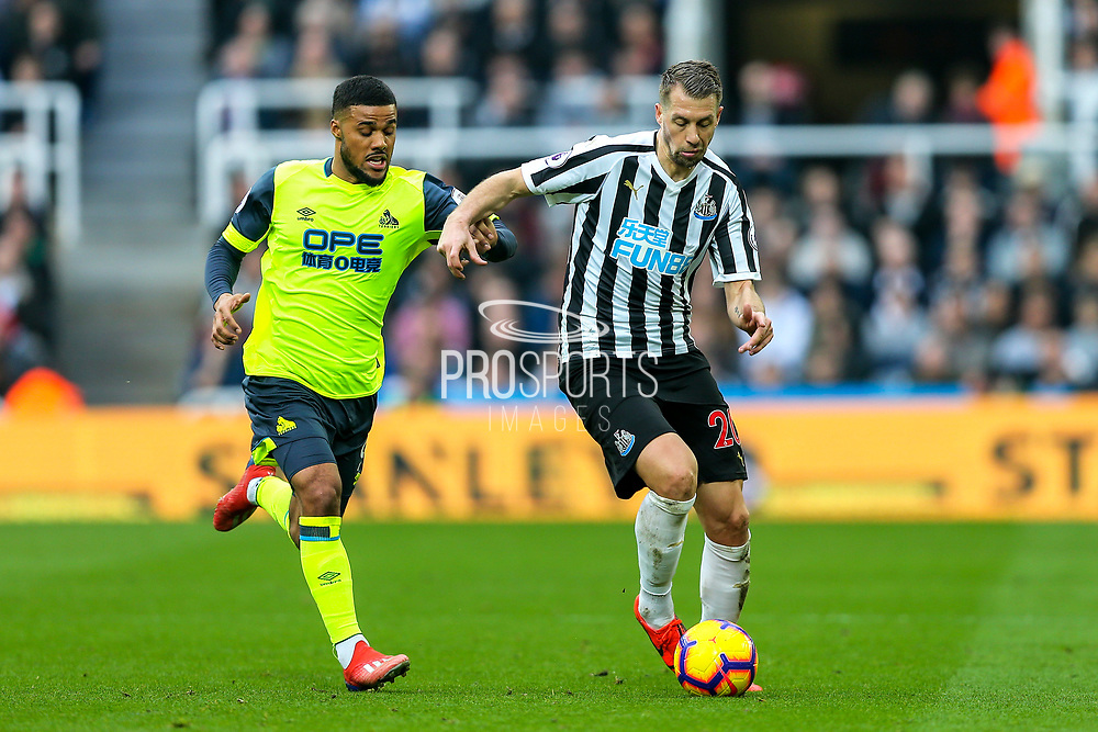 Florian Lejeune (#20) of Newcastle United battles for the ball with Elias Kachunga (#9) of Huddersfield Town during the Premier League match between Newcastle United and Huddersfield Town at St. James's Park, Newcastle, England on 23 February 2019.