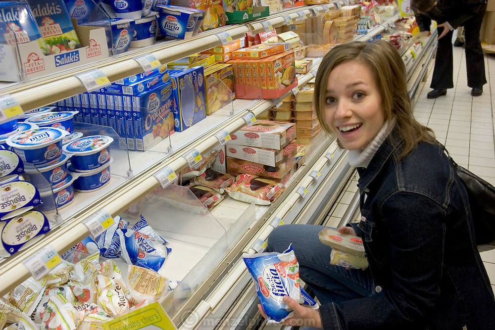 (MODEL RELEASED IMAGE). Delphine Le Moine, a dance student, buys mozzarella cheese at a supermarket in Paris. (Supporting image from the project Hungry Planet: What the World Eats.) The Le Moine family lives in the Paris suburb of Montreuil, France, and is one of the thirty families featured, with a weeks' worth of food, in the book Hungry Planet: What the World Eats.