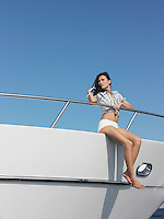 Young woman sitting at edge of yacht with legs dangling overboard