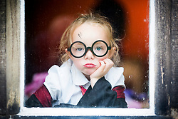 © Licensed to London News Pictures. 23/06/2017. Bolton UK. 4 year old Alice Burns dressed as Harry Potter waits inside for the rain to stop at the attempt to break the world record for the largest gathering of people dressed as Harry Potter that is taking place this morning at Smithhills Hall in Bolton. Bolton Museum & Library Services along with eleven local schools are coming together to try & break the record. Photo credit: Andrew McCaren/LNP