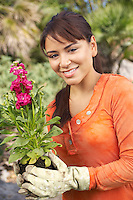 Woman wearing gardening gloves and holding flower