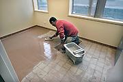 Nederland, Nijmegen, 8-11-2011Bouwvakkers zijn bezig met het bouwen van huizen in de waalsprong, onderdeel van de stadsuitbreiding van Nijmegen in Lent. Tegelzetter bezig met het voegen, inwassen, van een tegelvloer.Foto: Flip Franssen/Hollandse Hoogte