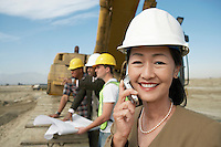 Surveyor in hard hat standing in front of heavy machinery Using Cell Phone on Construction Site