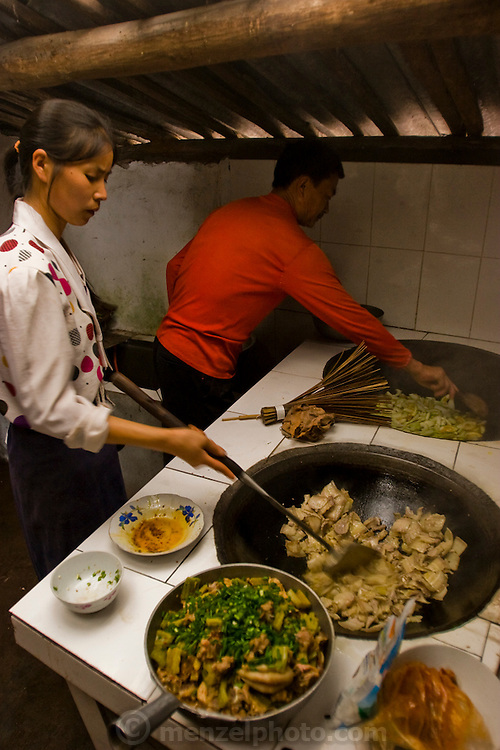 Widowed farmer Lan Guihua 's neighbors prepare lunch for foreign guests at her home in Ganjiagou Village, Sichuan Province, China.  (Lan Guihua is featured in the book What I Eat: Around the World in 80 Diets.) In this region, each rural family is its own little food factory and benefits from thousands of years of agricultural knowledge passed down from generation to generation.