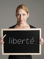 Portrait of young businesswoman holding blackboard with French text meaning Freedom